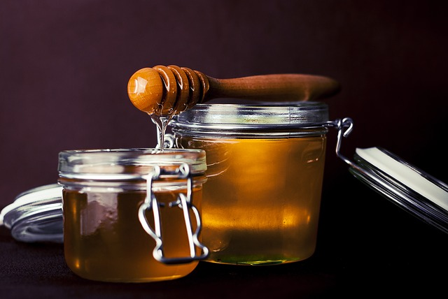 Two jars of golden honey with a honey dipper.